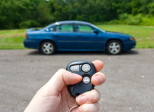 Hand holding keys to a car. A hand holding the keys to a car in the background Stock Photos