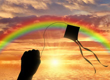 Hand holding kite in sky on sea sunset. Hand holding kite near sea and sun sets for horizon. Vacation concept Royalty Free Stock Image
