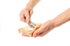 Hand holding knife spreading butter on bread Royalty Free Stock Photos