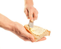 Hand holding knife spreading butter on bread Royalty Free Stock Images