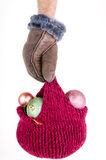 Hand holding a knitted hat with Christmas decorations Royalty Free Stock Images