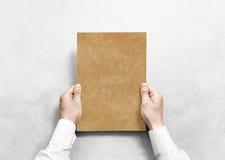 Hand holding kraft blank paper sheet mockup, Royalty Free Stock Photography