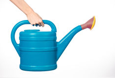 Hand holding a large blue plastic watering can  on  Royalty Free Stock Image