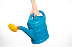 Hand holding a large blue plastic watering can  on white Royalty Free Stock Photography
