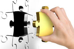 Hand holding last missing golden puzzle piece. Isolated on white Stock Photography