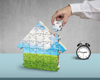 Hand holding the last piece of house puzzle with clock Stock Image