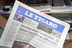 A hand holding Le Figaro newspaper. stock images