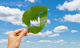 Hand holding leaf with a factory cutted against sky Stock Image