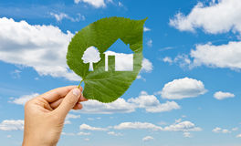 Hand holding leaf with a house cutted against sky Stock Images