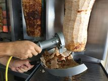Hand holding lectrical slicer cutting gyros stock image