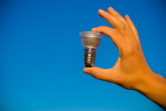 Hand holding LED lamp against blue sky Royalty Free Stock Photo
