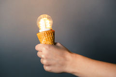 Hand holding led lamp in ice cream cone Royalty Free Stock Photo