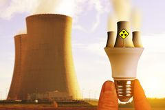 Hand holding LED light bulb with nuclear power plant at sunset. Stock Photo