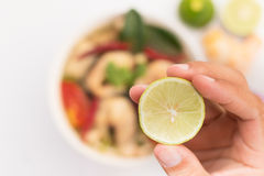 Hand holding a lemon to soup. Tom Yam Stock Photography
