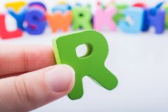 Hand holding Letter cube R of Alphabet royalty free stock photography
