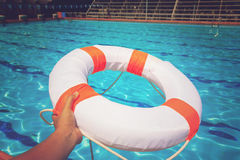 Hand holding Life buoy at swimming pool. Vintage Effect Royalty Free Stock Photos
