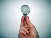 Hand holding light bulb. Closeup of hand holding small light bulb with white background Stock Images
