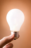 Hand holding light bulb on the beige background Stock Image