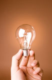 Hand holding light bulb on the beige background Royalty Free Stock Images