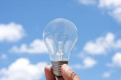Hand holding light bulb in blue sky Royalty Free Stock Images