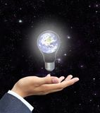 Hand holding light bulb earth (Earth view image fr Stock Photo