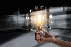 Hand holding light bulb with icons multimedia and customer network connection. On dark room background stock image