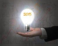 Hand holding 2015 light bulb illuminated dark doodles wall Royalty Free Stock Photo