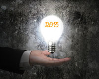Hand holding 2015 light bulb illuminated dark old concrete wall Stock Photography