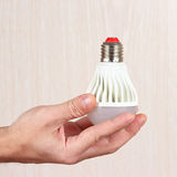 Hand holding a light bulb on light wood background Royalty Free Stock Photo