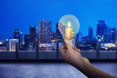 Hand holding light bulb with shining candle inside it. On modern city background Stock Image
