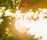 Hand holding light bulb with sunset, concept use alternative ene Royalty Free Stock Image