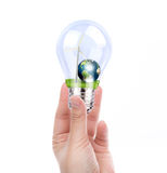 Hand holding light bulb with wind turbine and earth inside Royalty Free Stock Photo