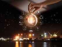 Hand holding light bulbl show the world`s consumption. Hand holding light bulb in front of global show the world`s consumption with icons energy sources for royalty free stock photos