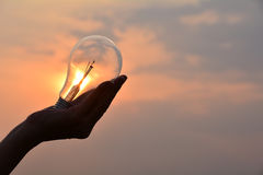 Hand holding light bulbs idea concept and silhouette style under Stock Photography