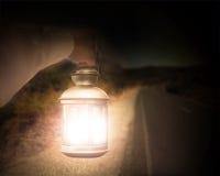 Hand holding light illuminating dark road at night Royalty Free Stock Images
