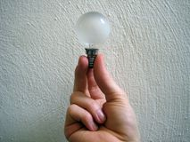 Hand holding lightbulb. Hand holding electric lightbulb with a textured wall for the background Royalty Free Stock Images