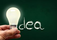 Hand Holding Lighted Bulb With Idea on Chalk Board and Copy Spac royalty free stock image