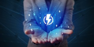 Hand holding lightning bolt. Hand in suit holding lightning bolt on his hand, green environment conceptn stock photo