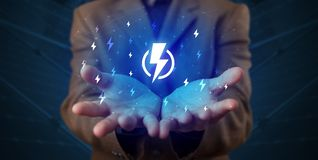 Hand holding lightning bolt. Hand in suit holding lightning bolt on his hand, green environment conceptn stock images