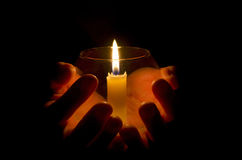 Holding the Light. A hand holding a lit candle in the dark Royalty Free Stock Images
