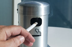 Hand holding lit cigarette in ash tray Stock Photos