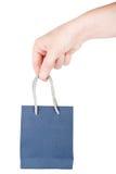 Hand holding little blue gift bag Stock Photos