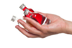 Hand holding little bottles. Of liquor Stock Image