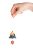 Hand holding little ceramics bell Royalty Free Stock Images