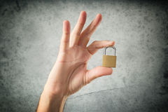 Hand holding locked padlock Stock Images