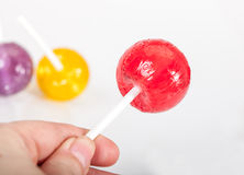 A hand holding a lollipop Stock Photos