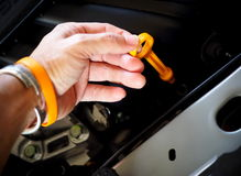 Hand holding lubricant oil level check dipstick Royalty Free Stock Image