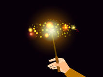 Hand holding a magic wand. Magic bright light with sparks. Royalty Free Stock Photo