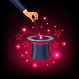 Hand holding magic wand over a magical top hat. Magician hand holding a magic wand and waving it over a magical top hat with star sparkles. Flat vector Stock Photo