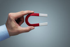 Hand holding magnet. Close up of male hand holding horseshoe magnet Stock Photography